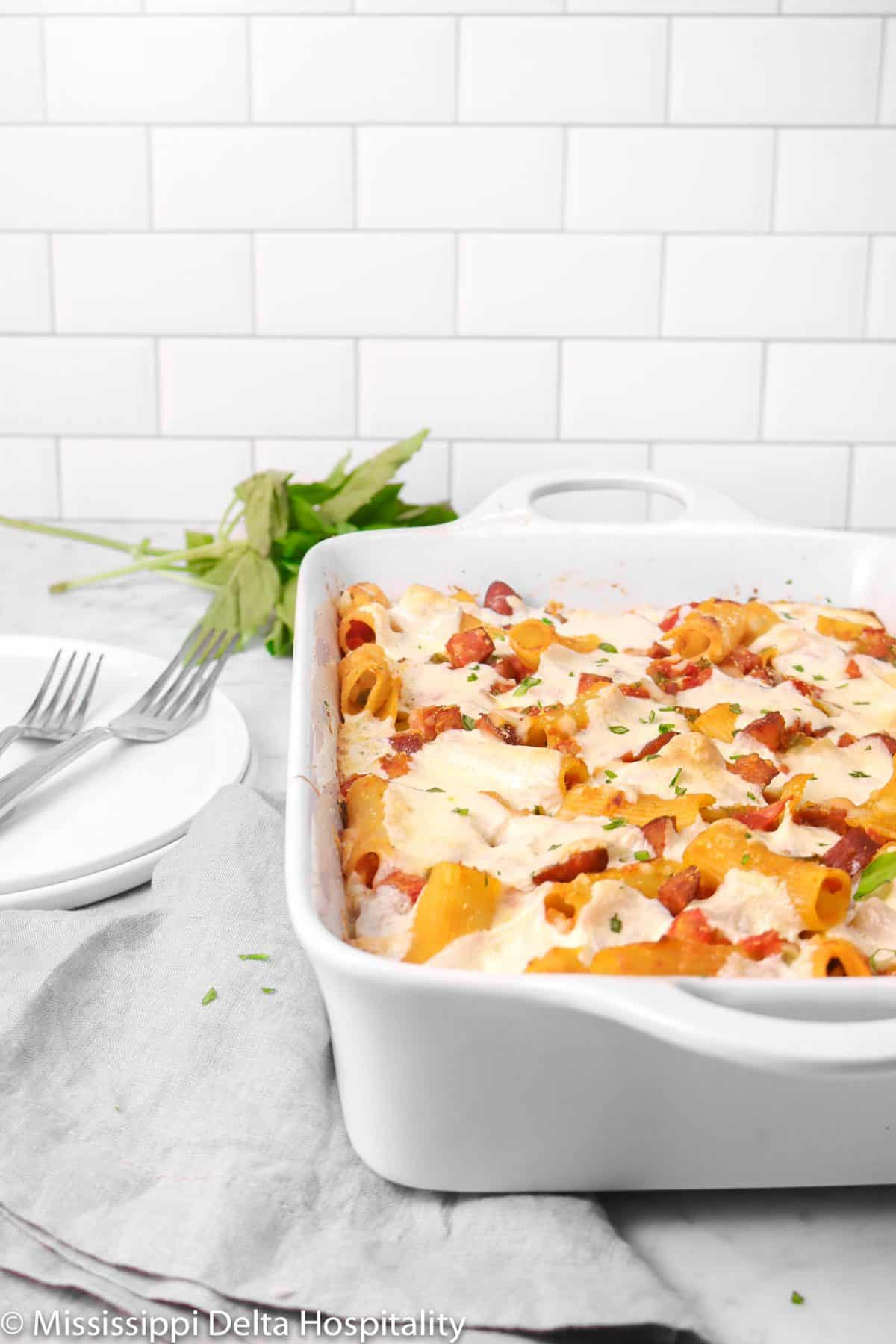 baked rigatoni on a marble board with two plates