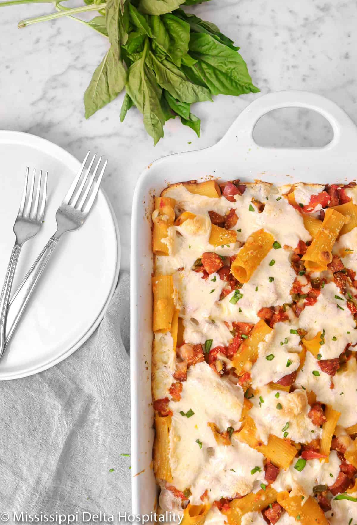 baked rigatoni on a marble counter with white plates, two forks, and basil