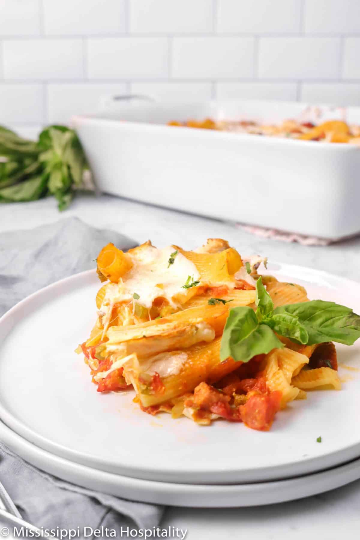 baked rigatoni on a white plate with a grey napkin and two basil leaves
