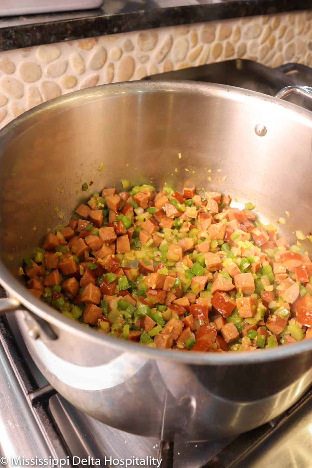 vegetables and andouille sausage in a pot