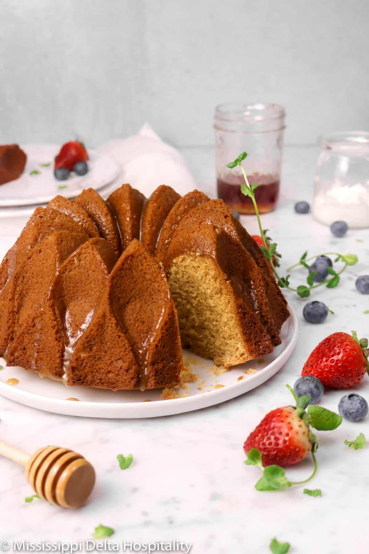 honey bundt cake on a white plate with a slice taken out