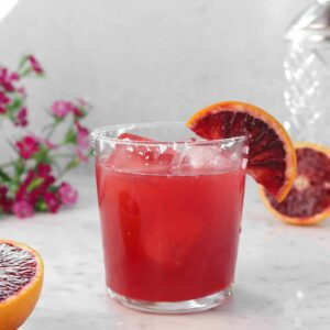 blood orange margarita on a marble table with flowers and blood orage slices