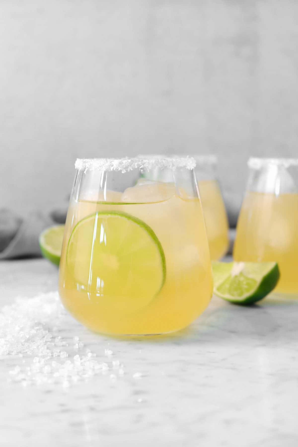 three classic of lime margarita on a marble board with salt