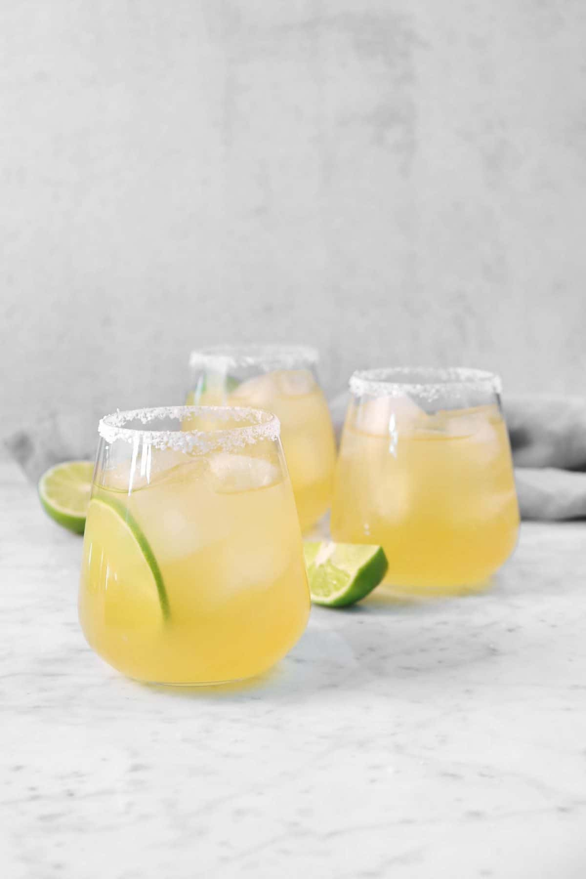 three lime margaritas on a marble board with slices of lime and a grey napkin