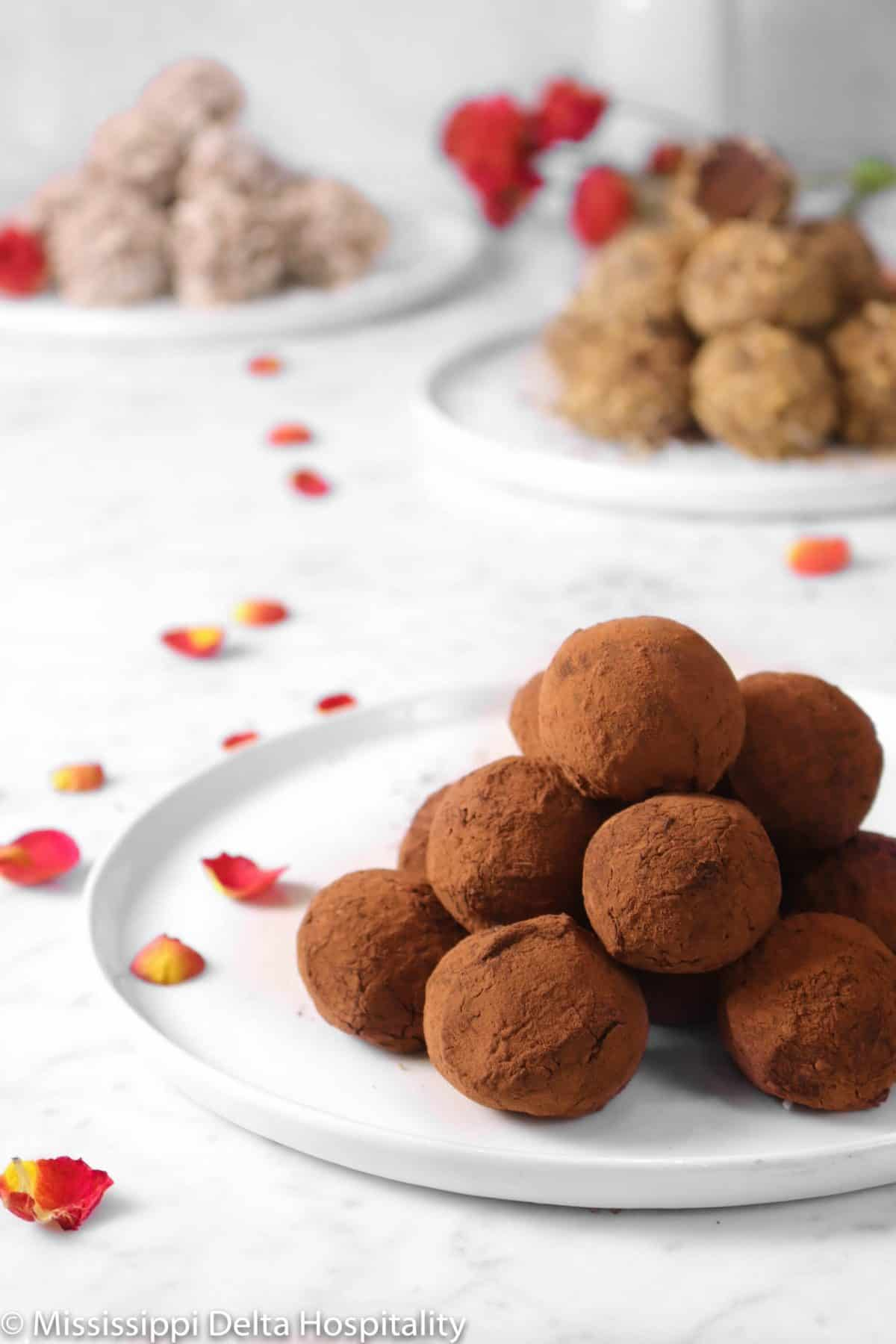chocolate truffles on three different white plates on a marble board with red rose petals and a glass of milk
