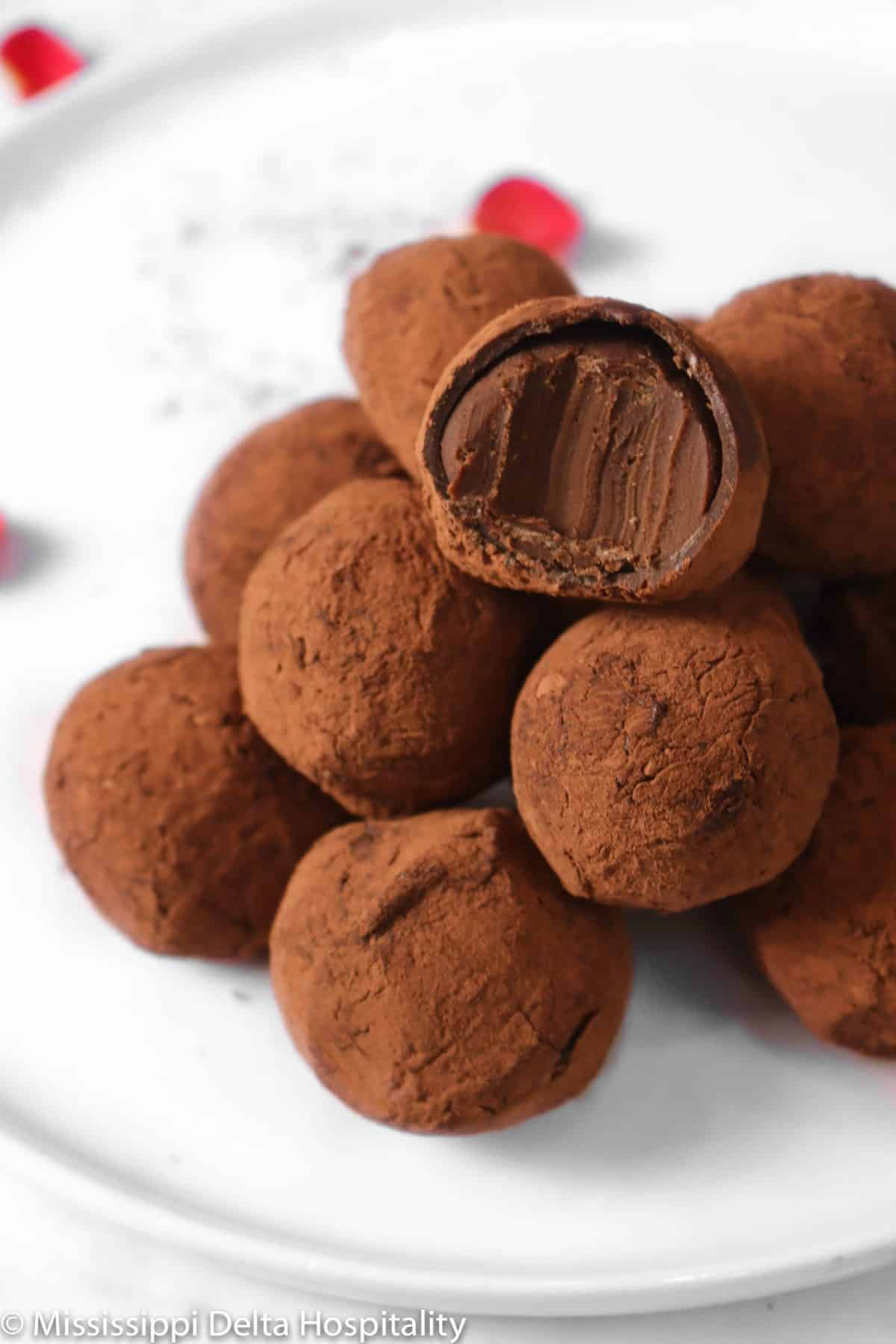 a stack of dark chocolate truffles covered in cocoa powder with a bite taken out of one on a white plate