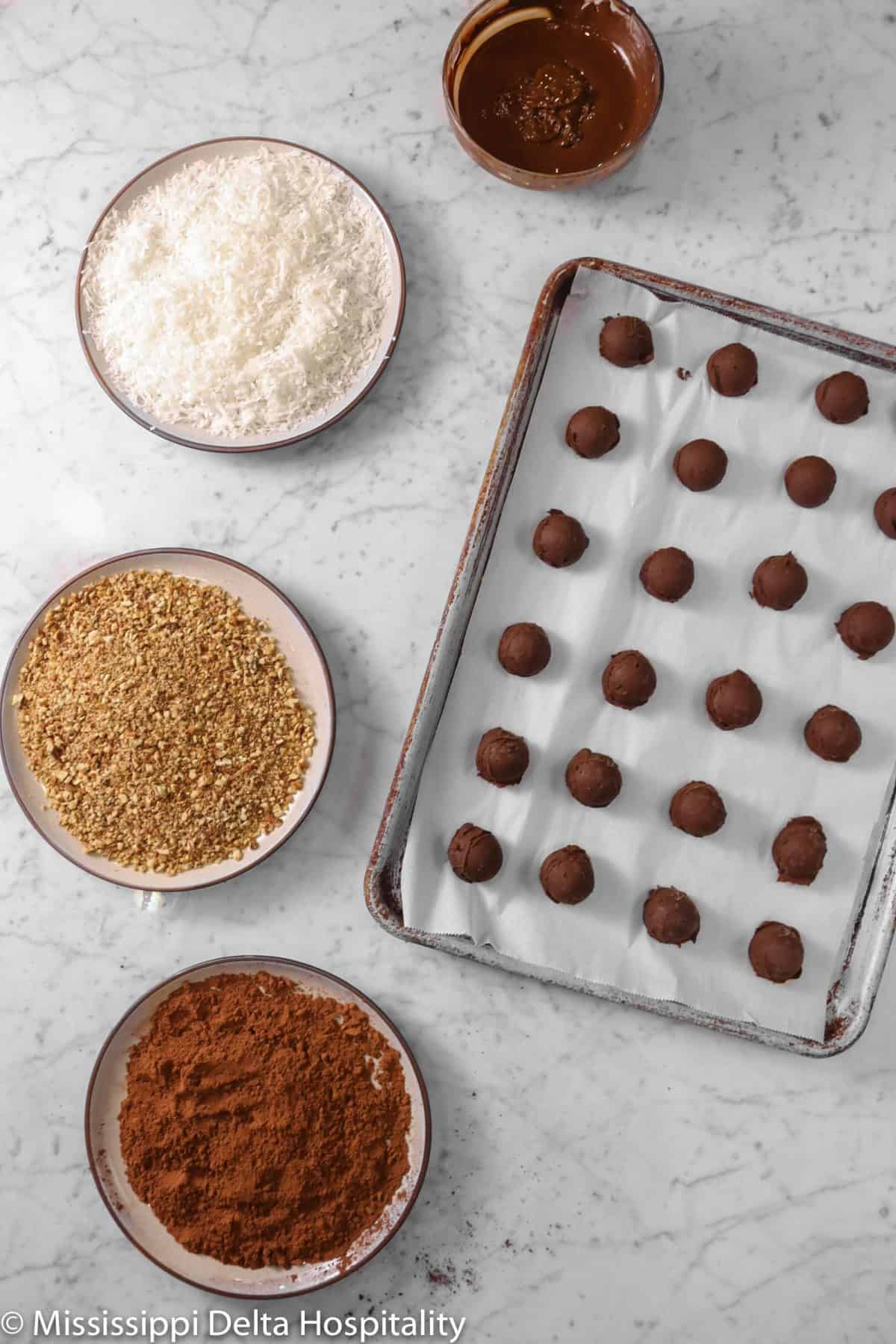 tray full of ganache balls with three plates of cocoa powder, toasted pecans, coconut flakes, and a bowl of melted chocolate