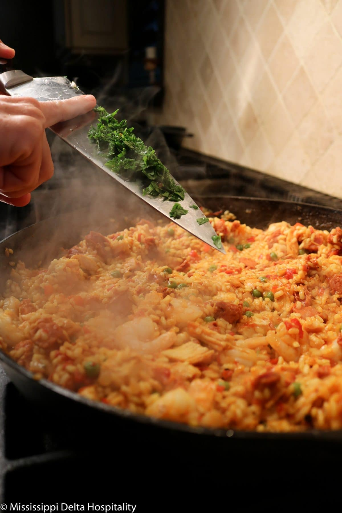 parsley being added to paella
