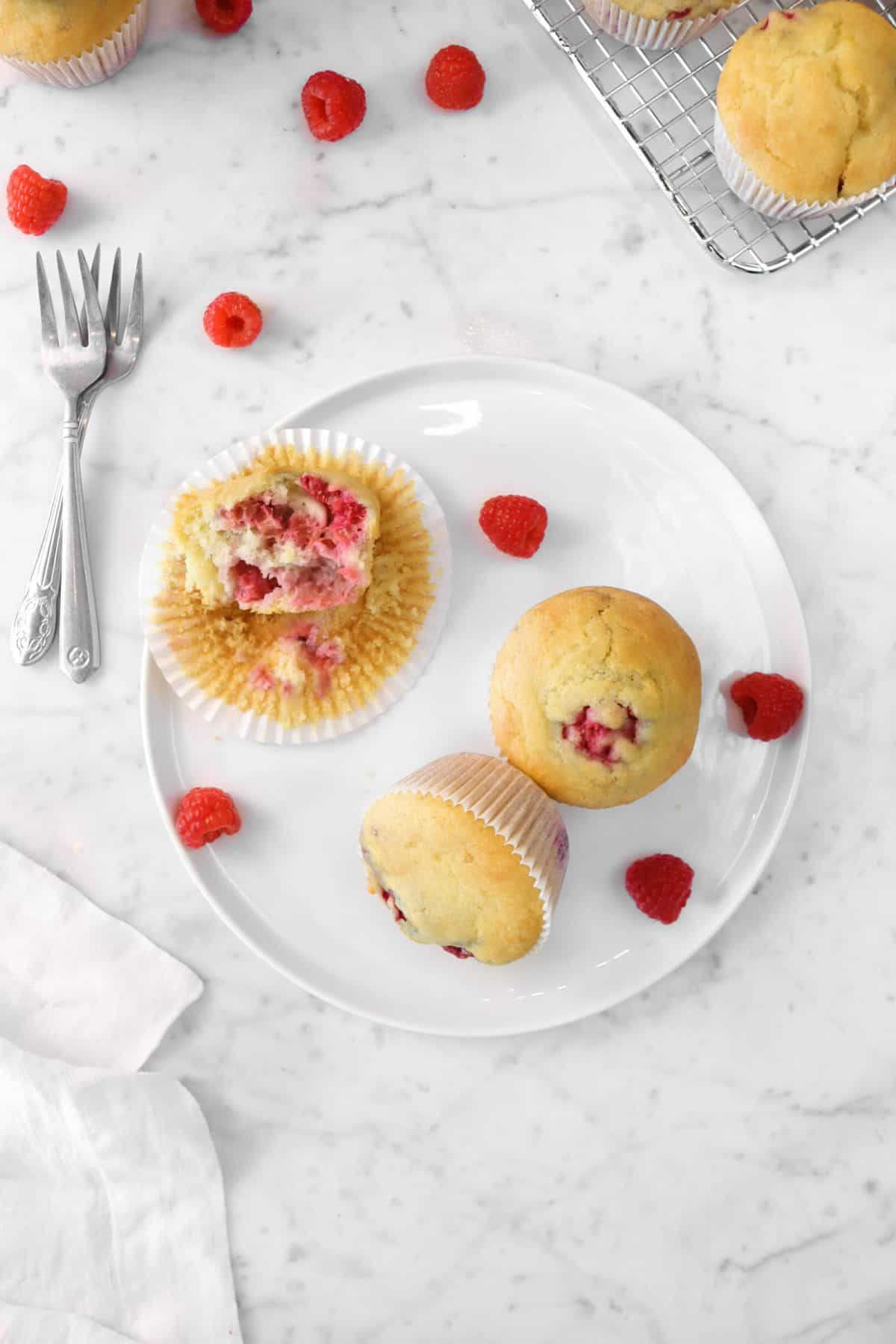 three muffins on a white plate with raspberries, two forks, and a napkin