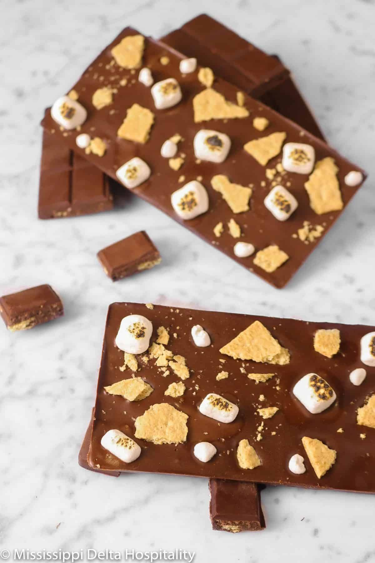 four homemade chocolate bars with marshmallows and graham crackers with one broken up