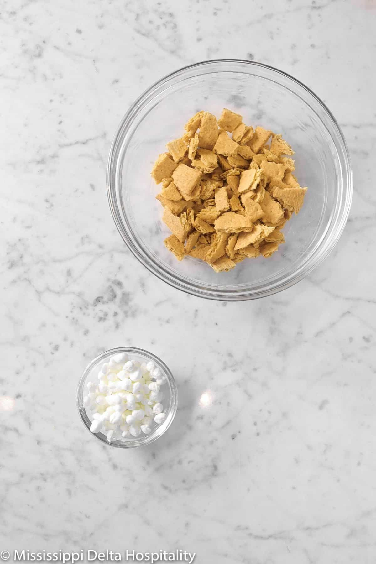 Graham crackers broken up in a small bowl and a small bowl of chopped marshmallows