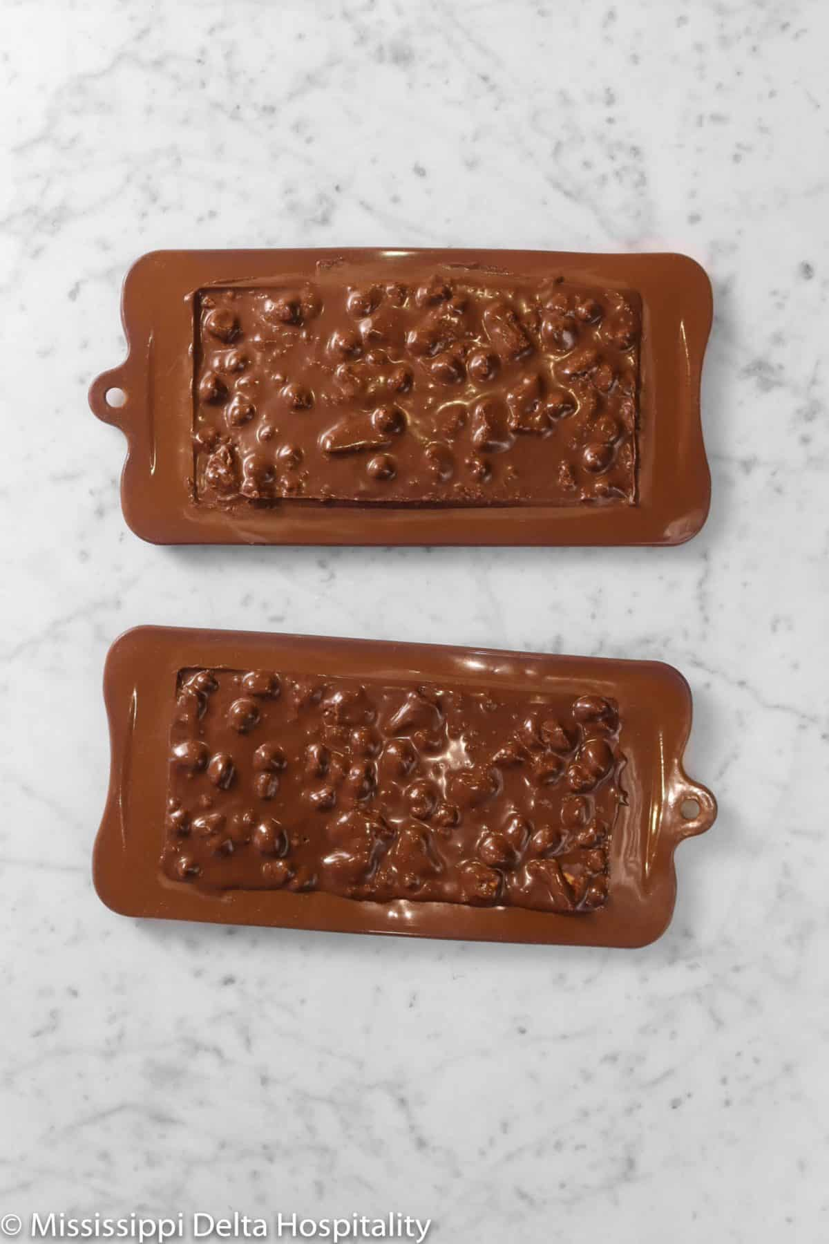 two chocolate bars in a chocolate molds on a marble table