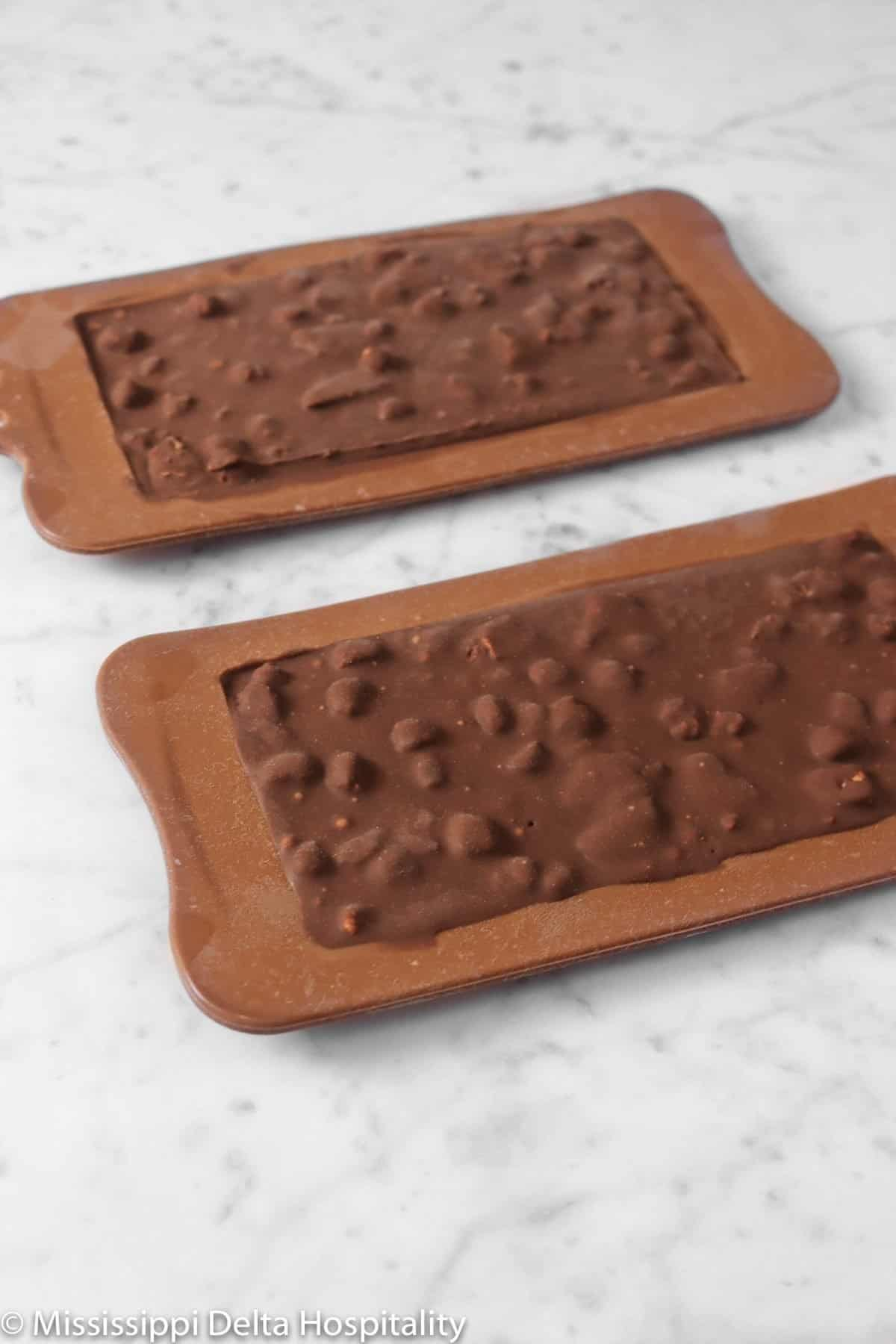 chocolate bars in molds on a marble table