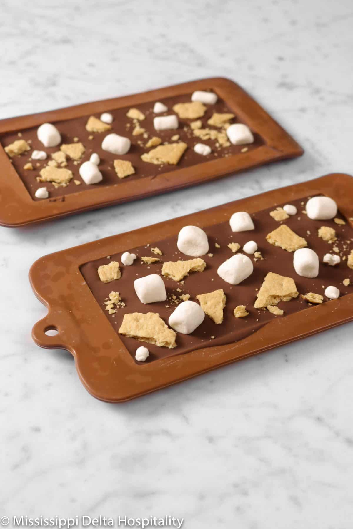 two chocolate bars in molds on a marble table