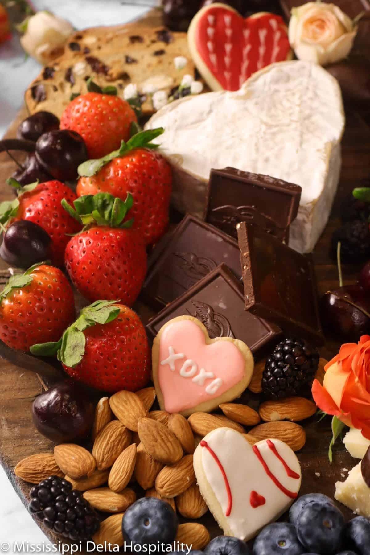 wood serving tray with almonds, strawberries, cherries, blueberries, blackberries, heart shaped brie, and fresh flowers