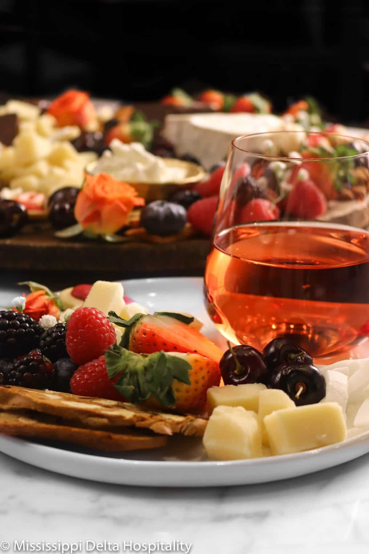 a white plate with cheeses, berries, cookies, and a glass of wine with the cheese board behind it