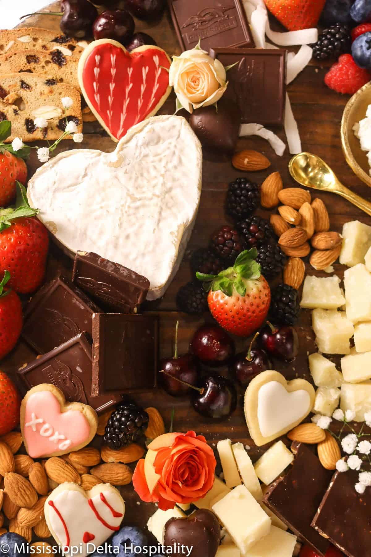 wood serving tray with cheeses, berries, chocolates, almonds, fresh flowers, cinnamon cookies, and cugar cookies