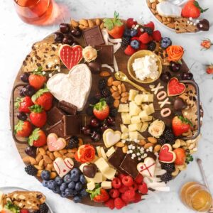 wood serving board with cheese, chocolates, heart shaped cookies, berries, and fresh flowers on a marble board with two plates and glasses of rosé and a jar of honey