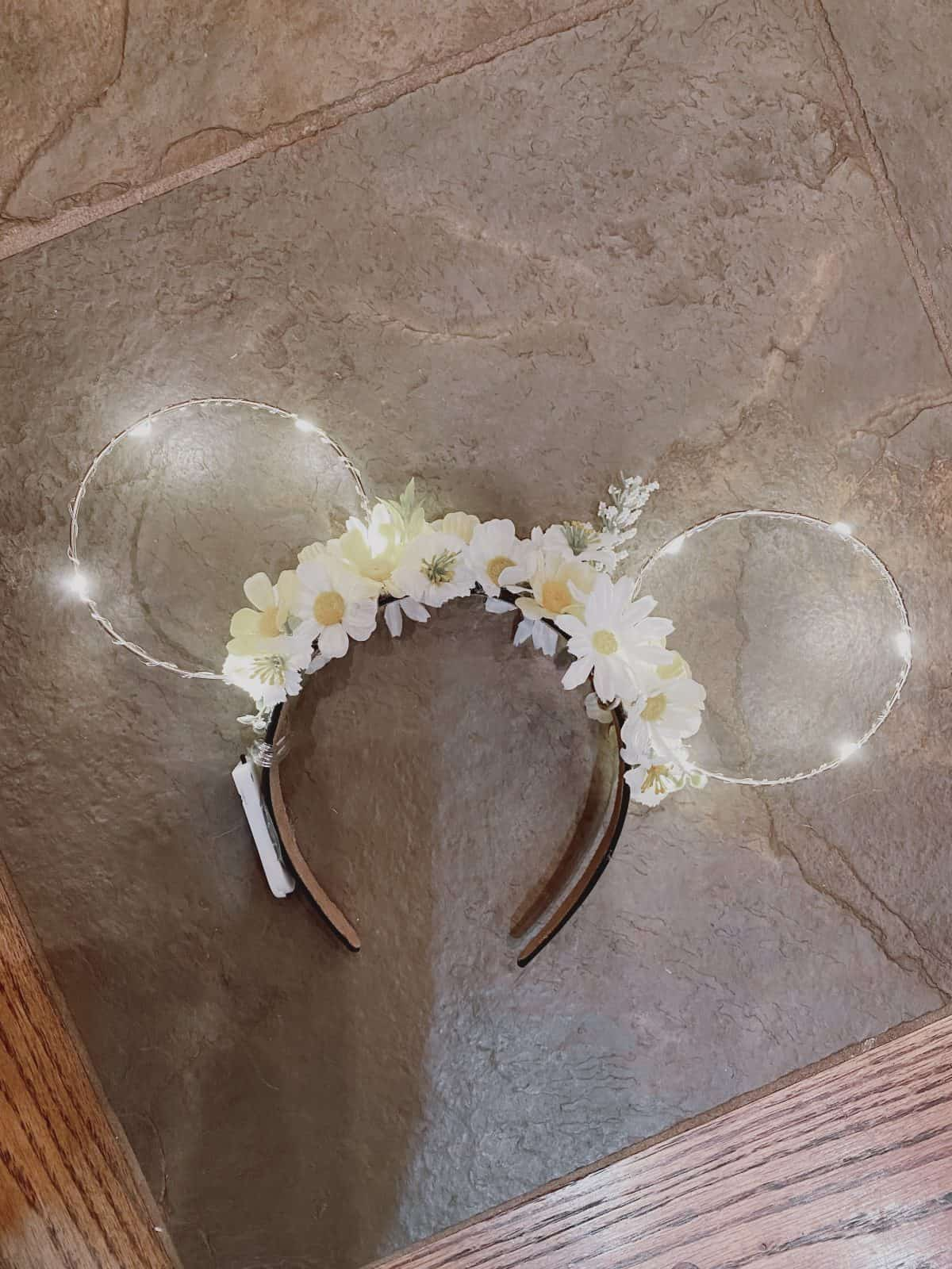 wire mickey ears with flowers and fairy lights on a grey tile floor