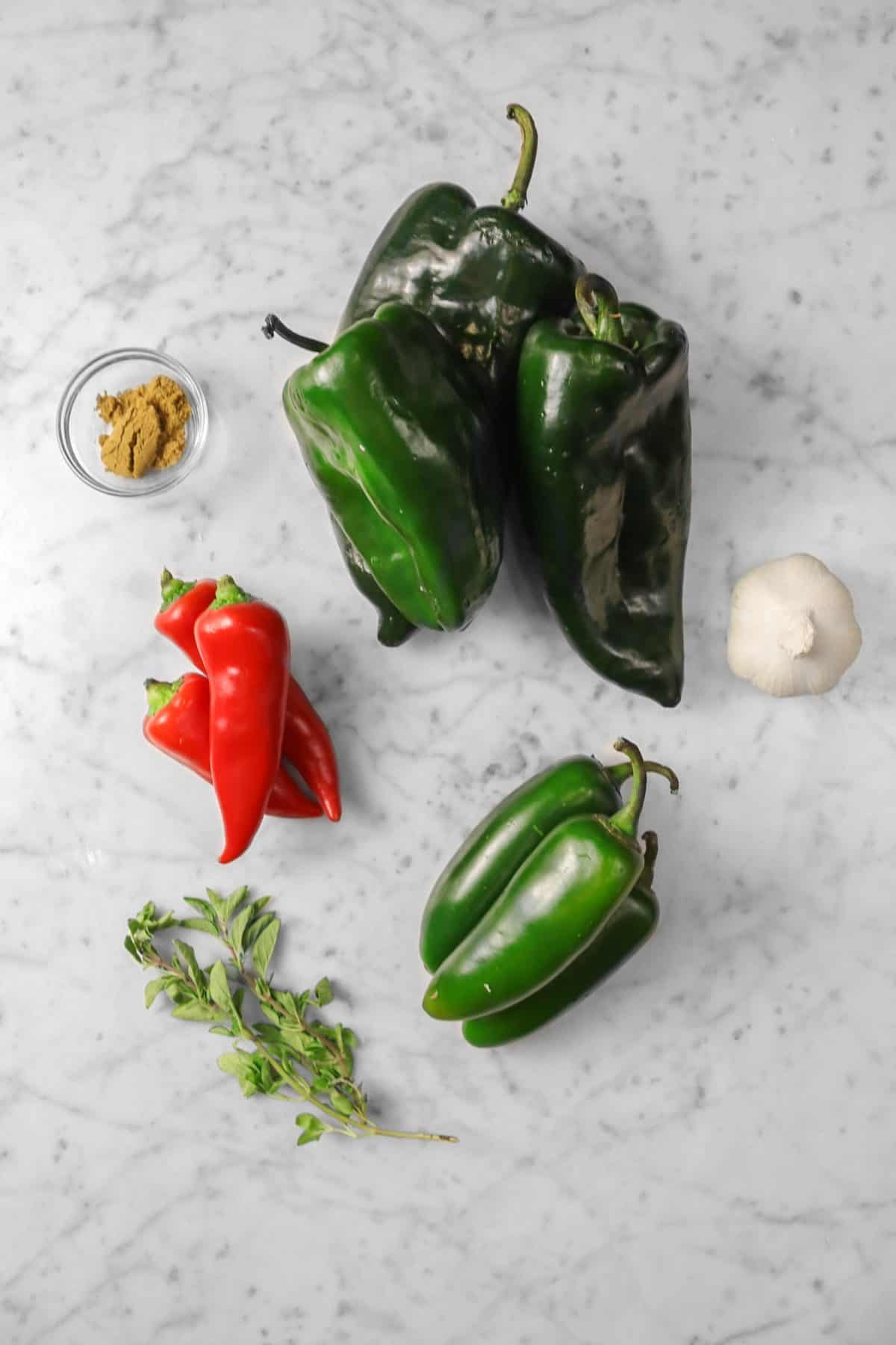 pablano chili's, jalapeno's, and red chili's on a marble board with cumin, oregano, and a head of garlic