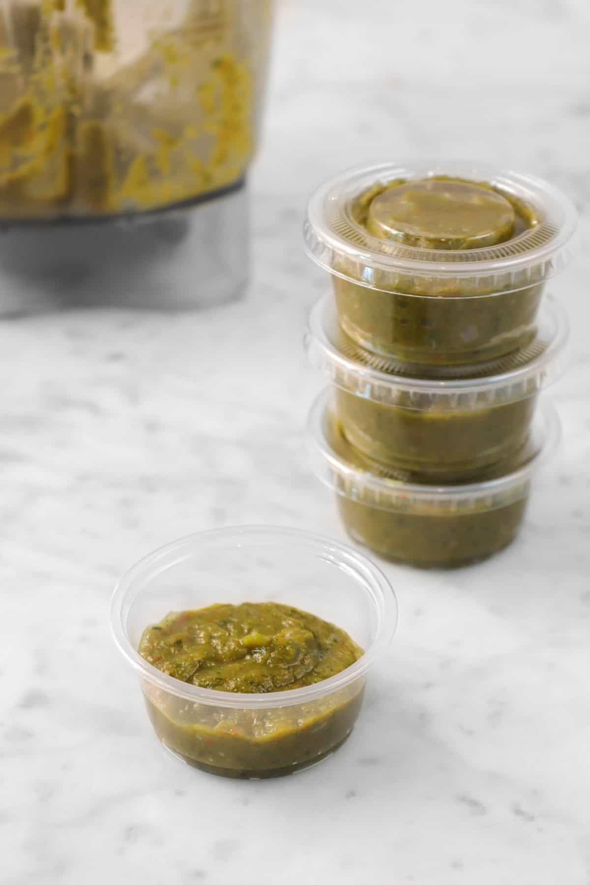 chili paste in small plastic containers on a marble counter with a blender in the background