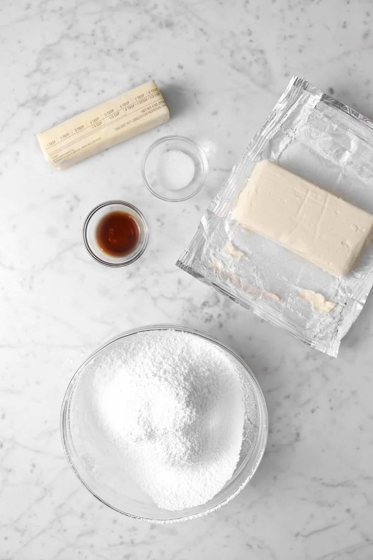 ingredients for cream cheese frosting on a marble counter