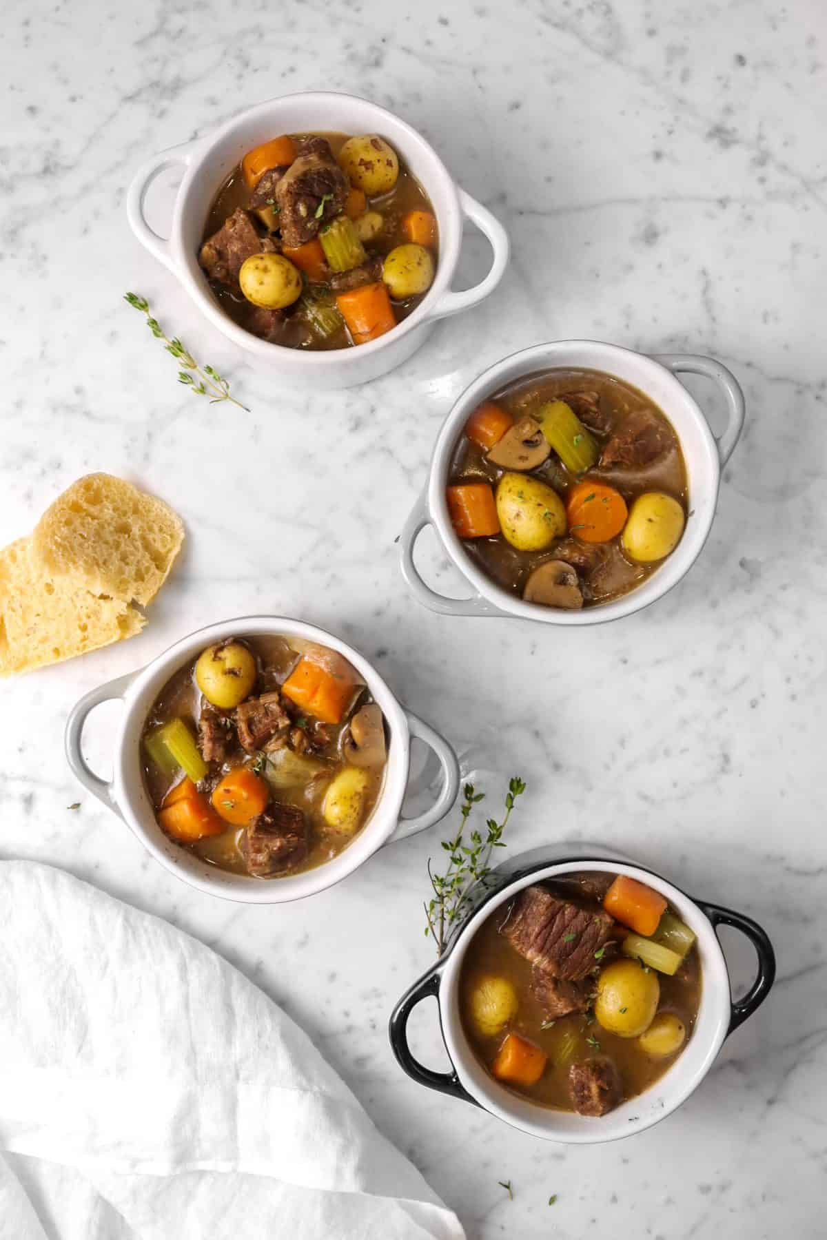 four cocottes of beef stew on a marble table with thyme sprigs, bread, and a white napkin