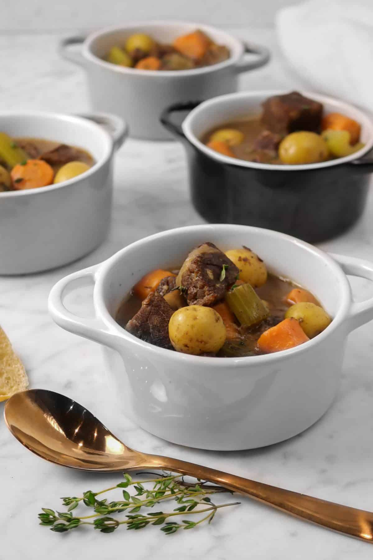four bowls of beef stew with a copper spoon and thyme sprigs