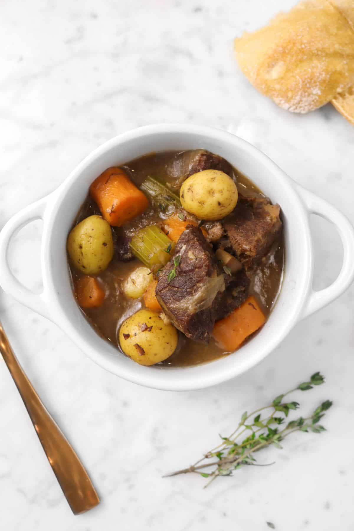 bowl of beef stew on a marble table with a copper spoon,