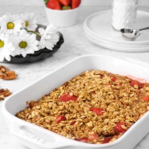 strawberry oatmeal bake in a white casserole dish on a marble counter with flowers, strawberries, white plates, and powdered sugar in the background