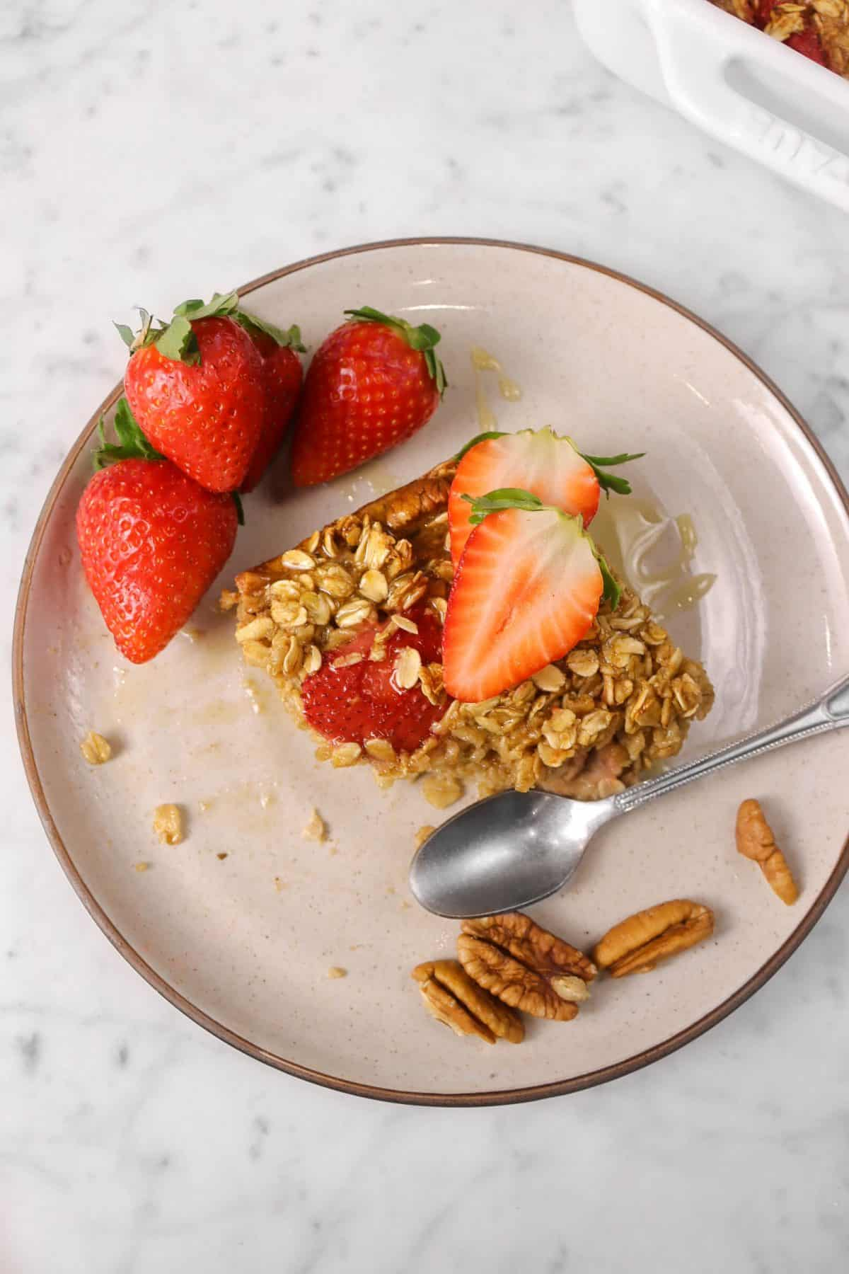 slice of oatmeal bake on a plate with strawberries and nuts