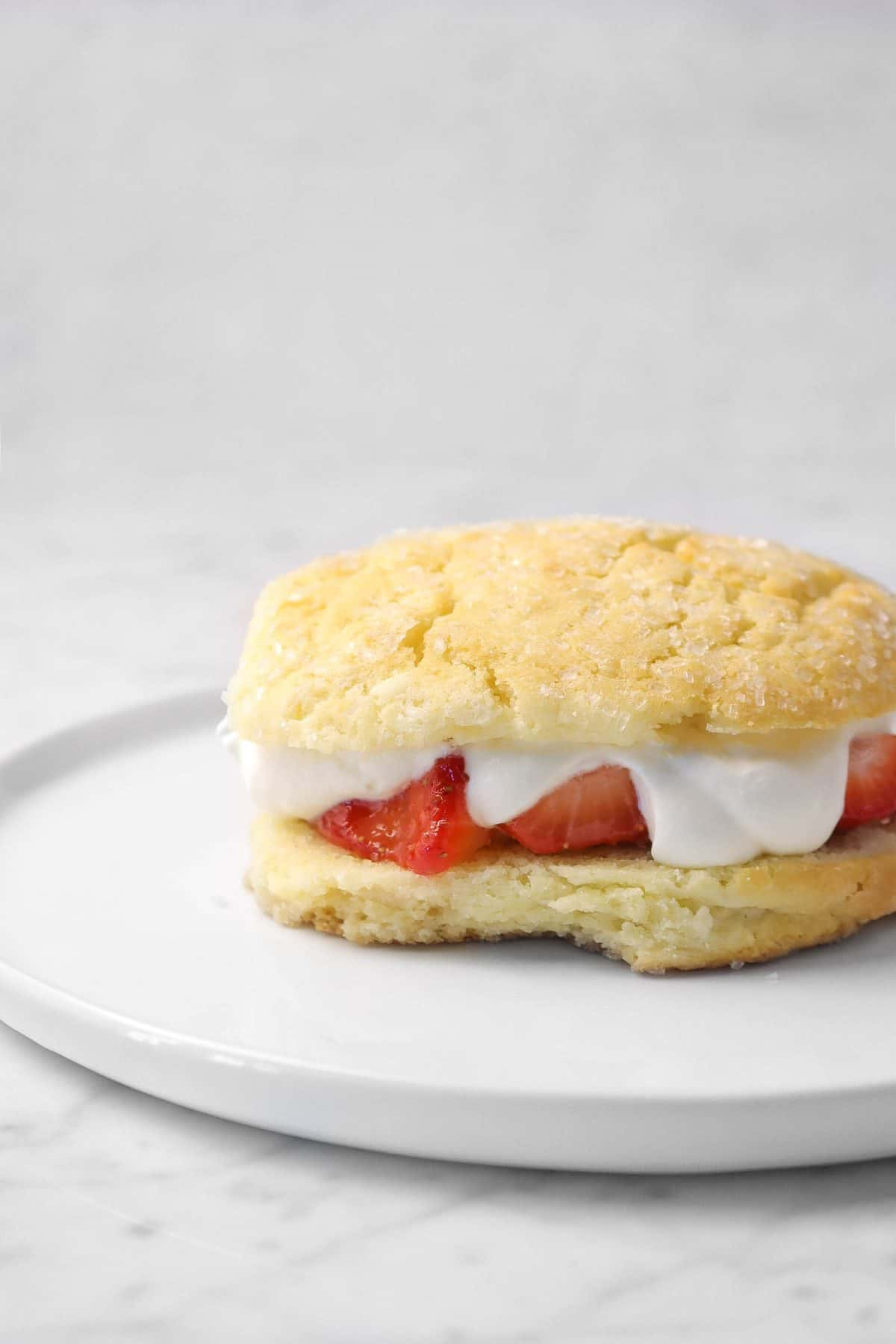 top half of shortcake added on top of whipped cream
