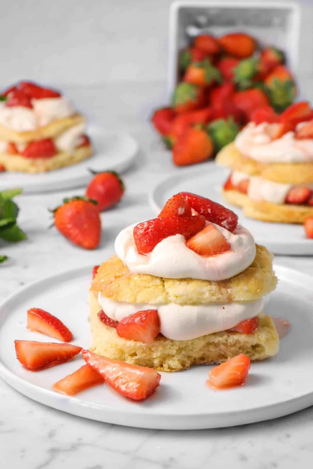 three strawberry shortcakes on a white plate with a white basket of strawberries