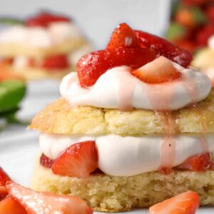 strawberry shortcake on a white plate with chopped strawberries on the plate with another shortcake in the background