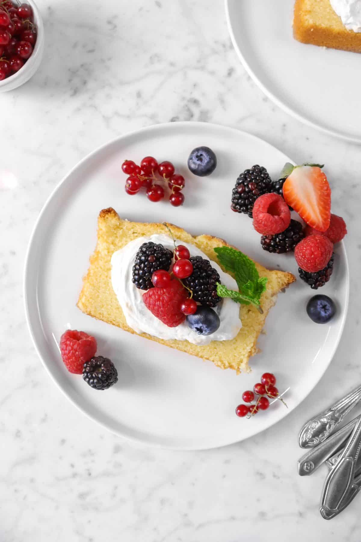 slice of pound cake with berries and chantilly cream on a white plate