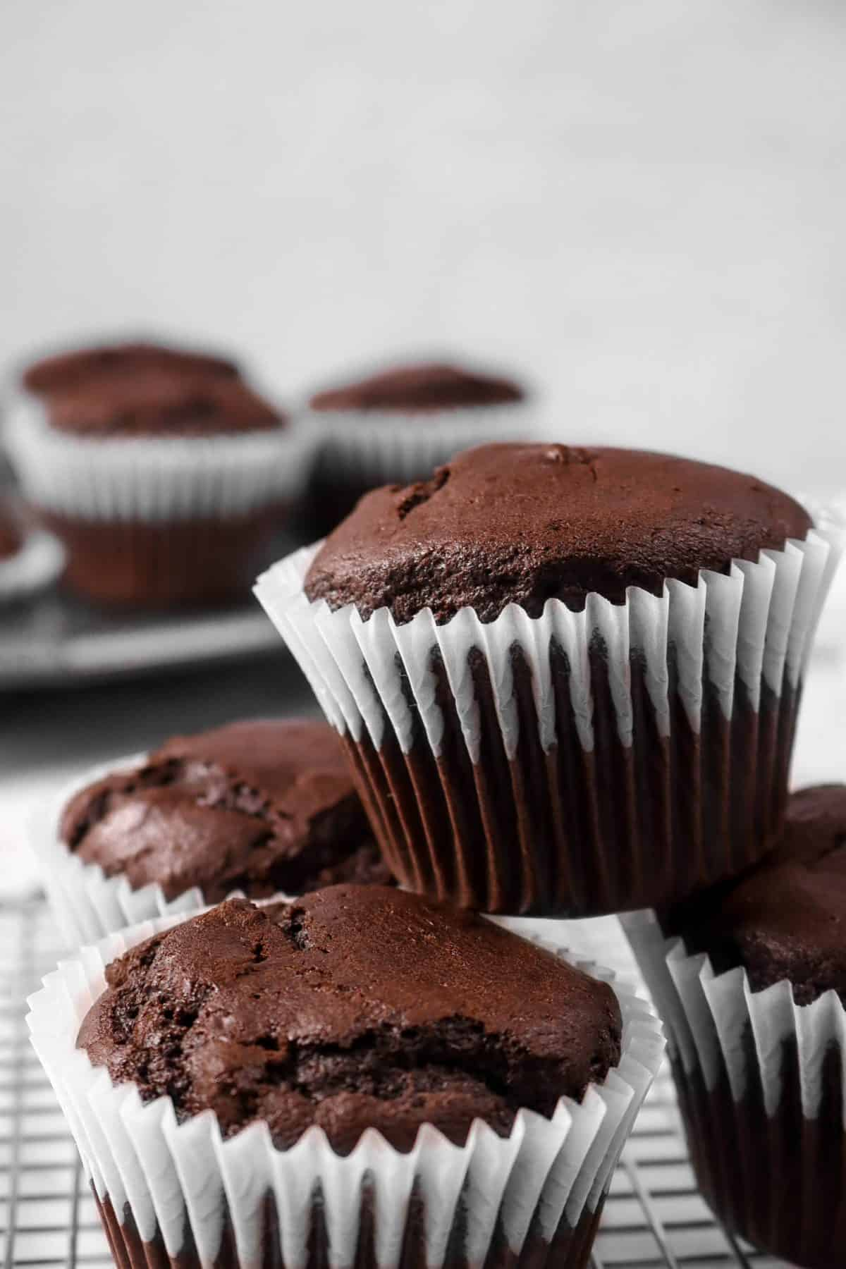 four chocolate muffins stacked on top of each other with a pan of muffins behind it