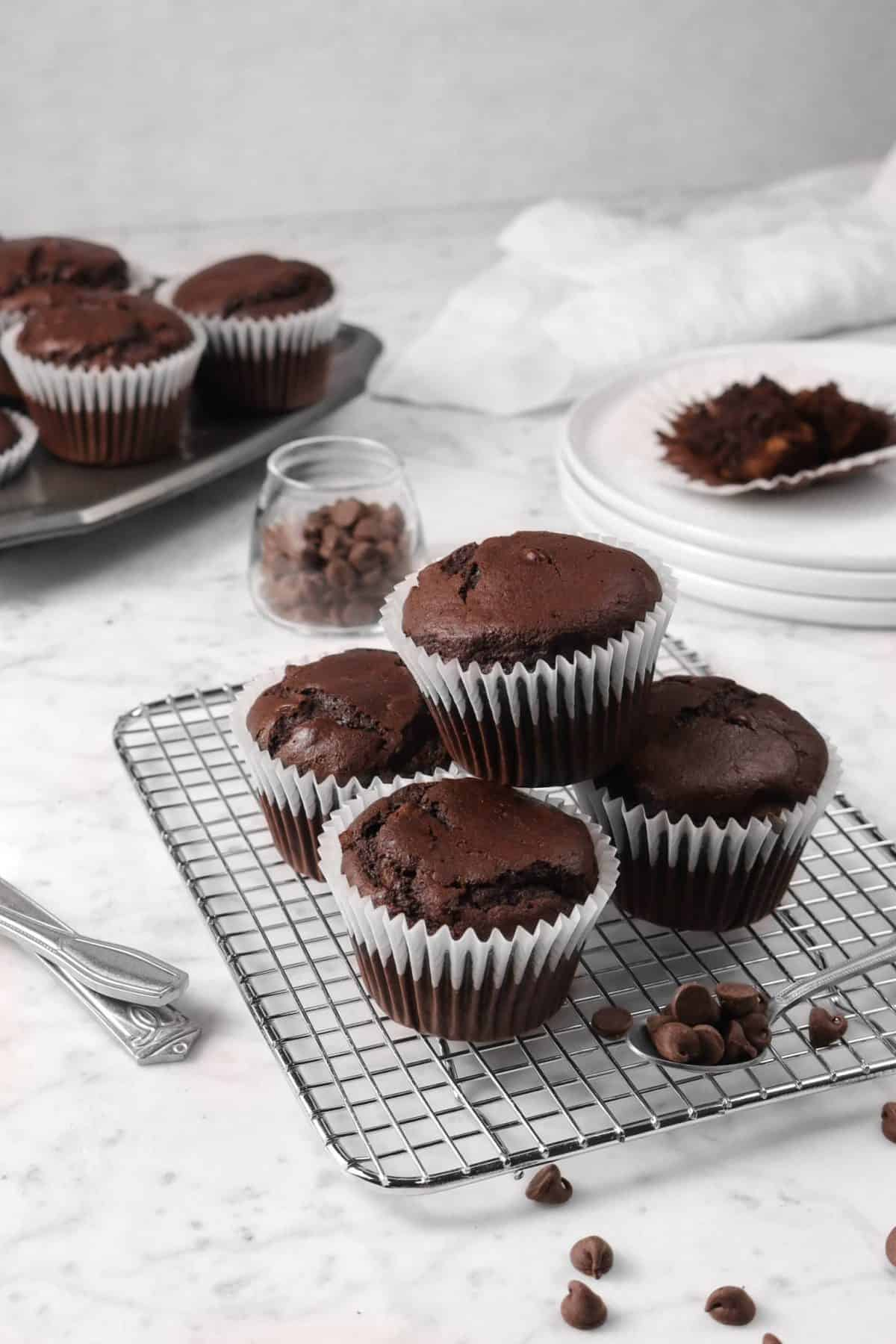 chocolate muffins on a cooling rack with chocolate chips and white plates and a napkin