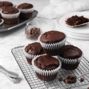 chocolate muffins on a cooling rack with chocolate chips and white lates and a napkin