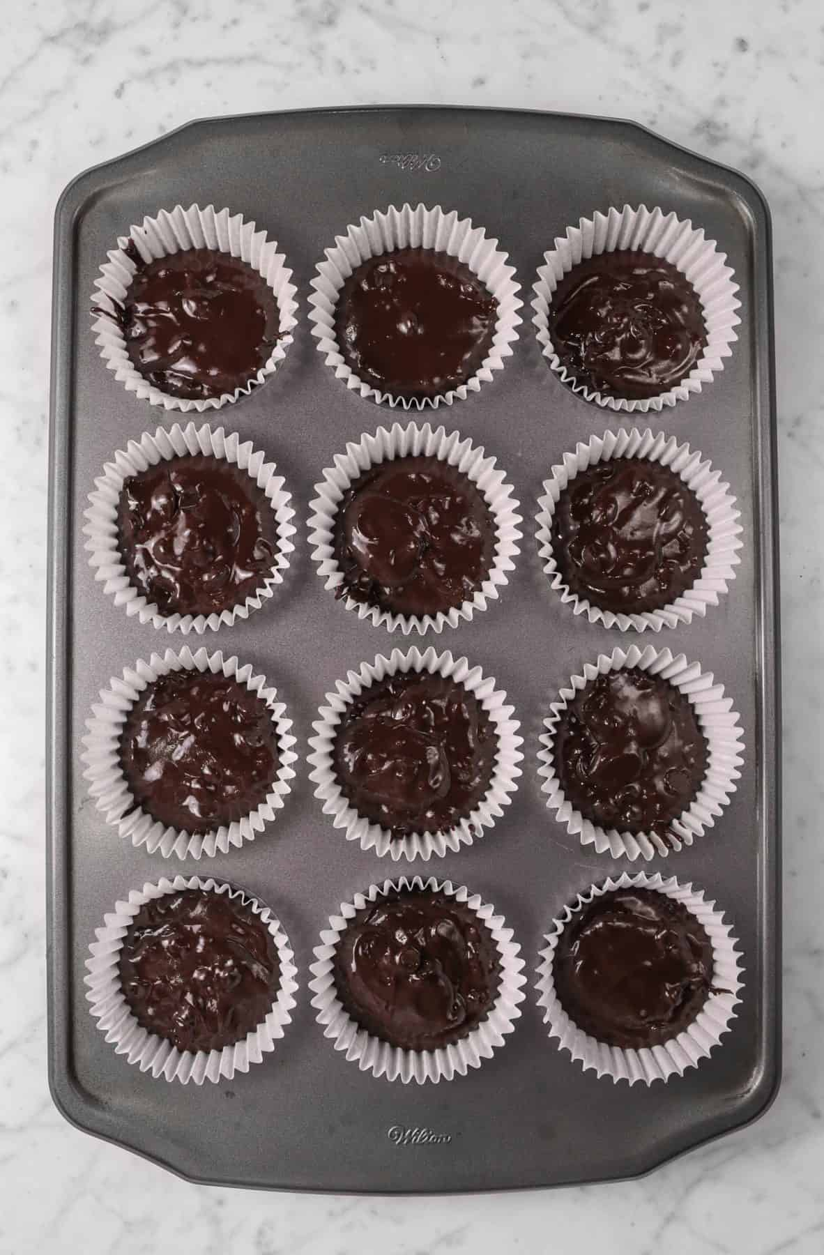 batter added to muffin tins on a marble counter