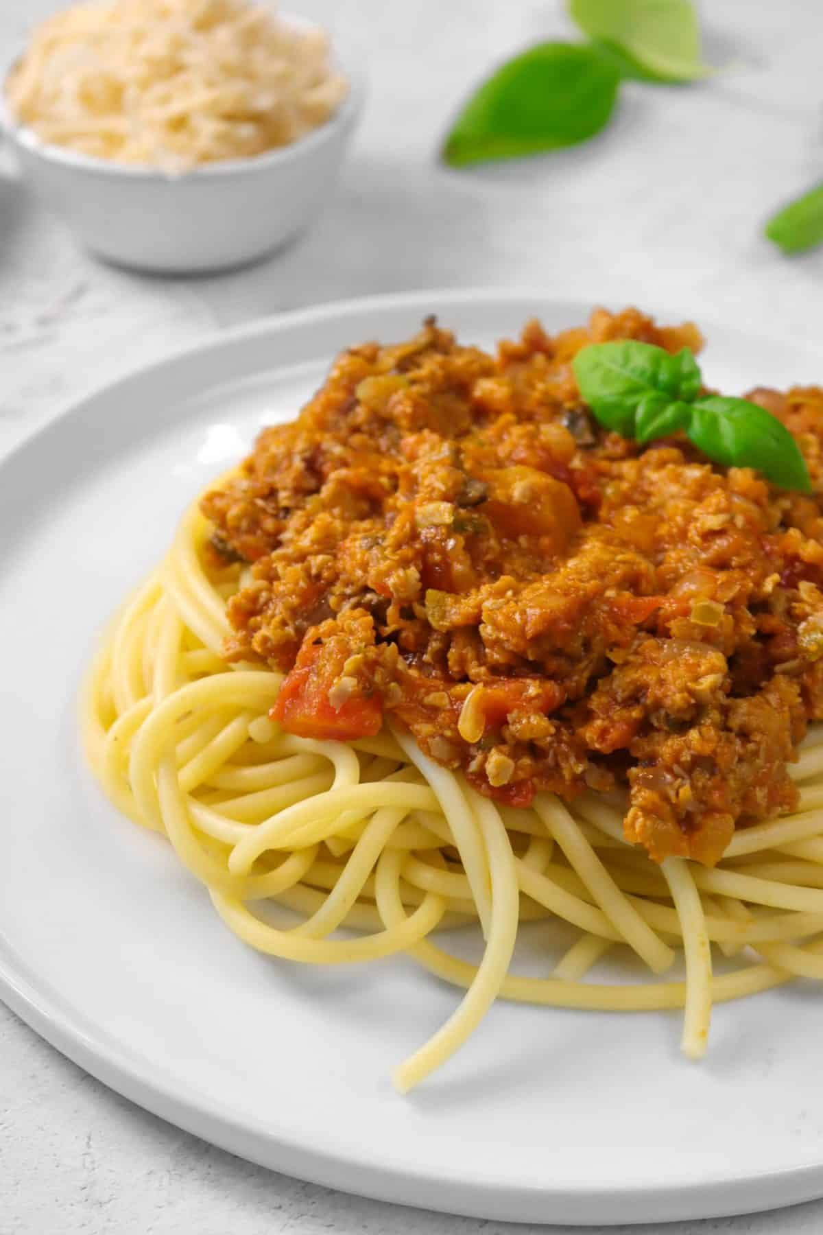 vegan spaghetti sauce on a white plate with pasta and basil and a bowl of vegan parmesan