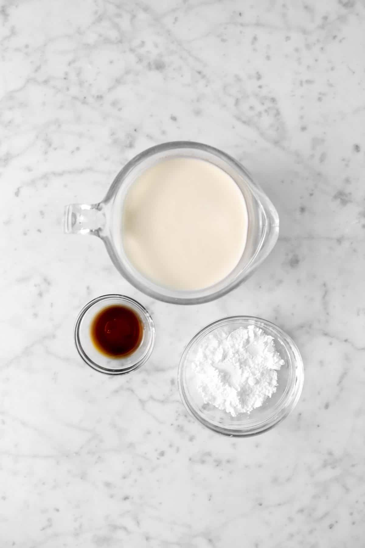 glasses of vanilla, powdered sugar, and heavy cream on a marble counter