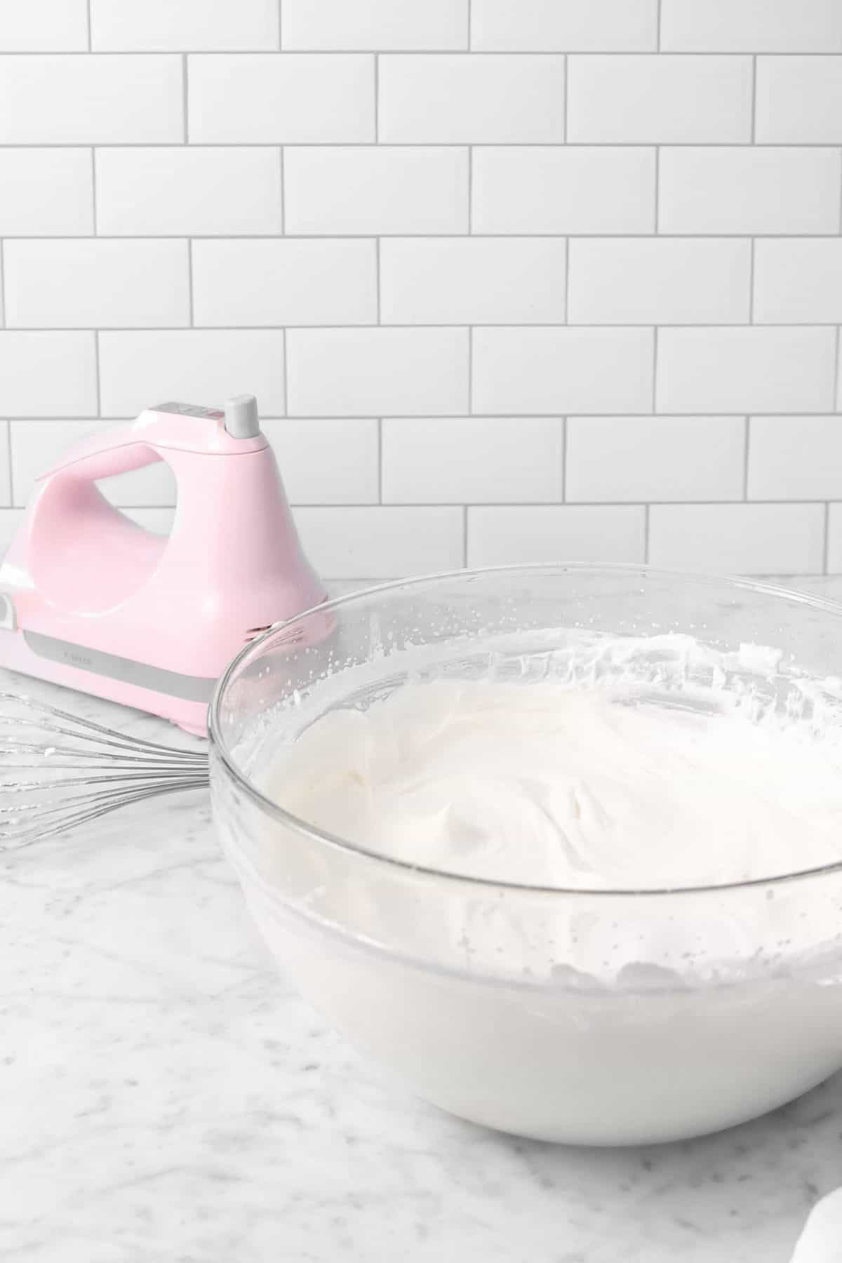a bowl full of chantilly cream with a pink electric mixer on a marble counter