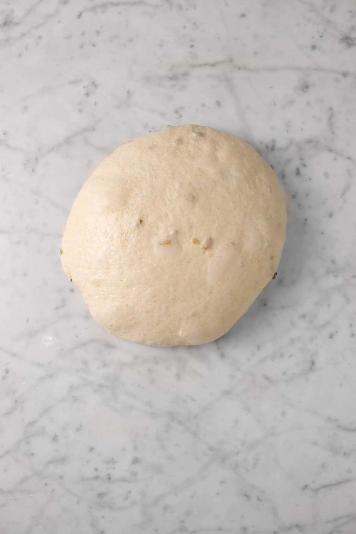 dough smoothed out into a small boule on a marble counter