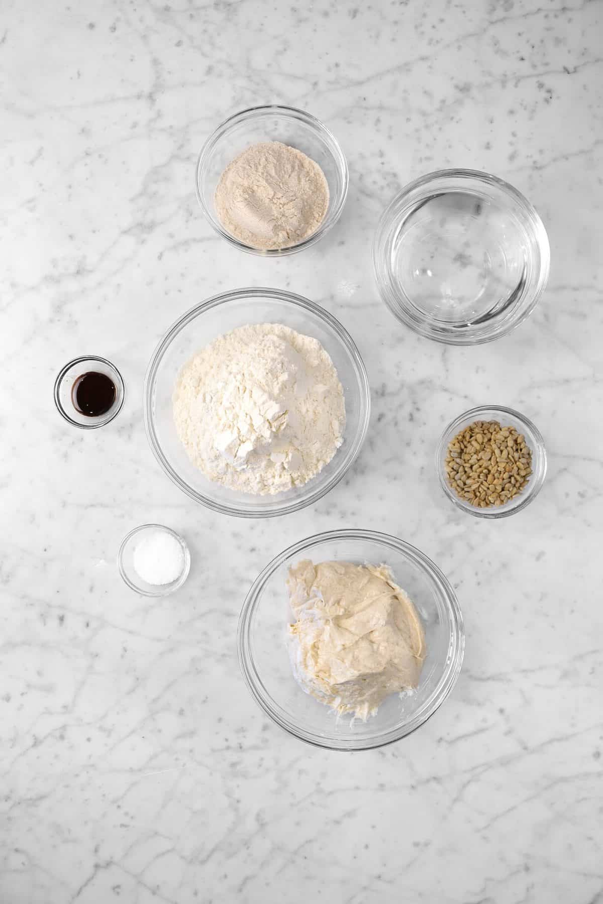 ingredients for sourdough whole wheat bread with sunflower seeds on a marble counter