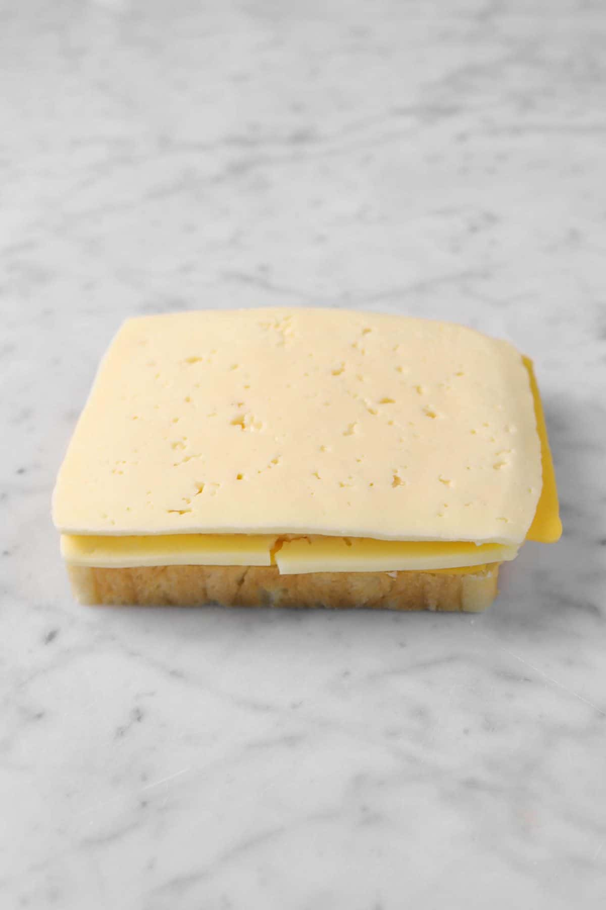 cheese slices on a slice of bread on a marble counter