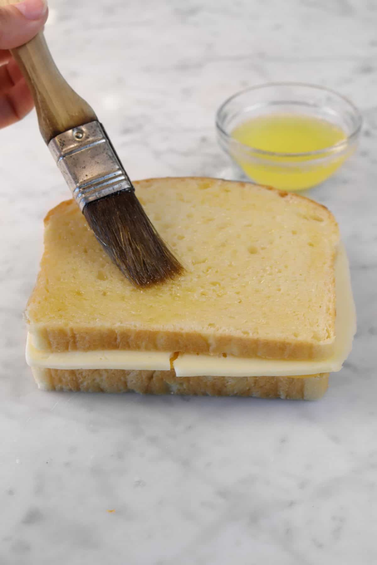 butter being brushed onto cheese sandwich