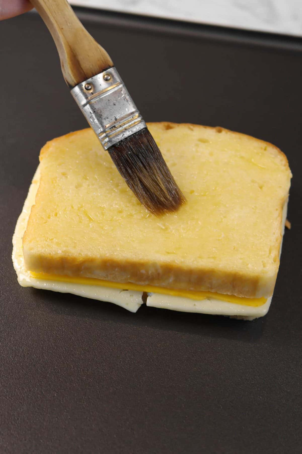 butter being brushed onto bread slice