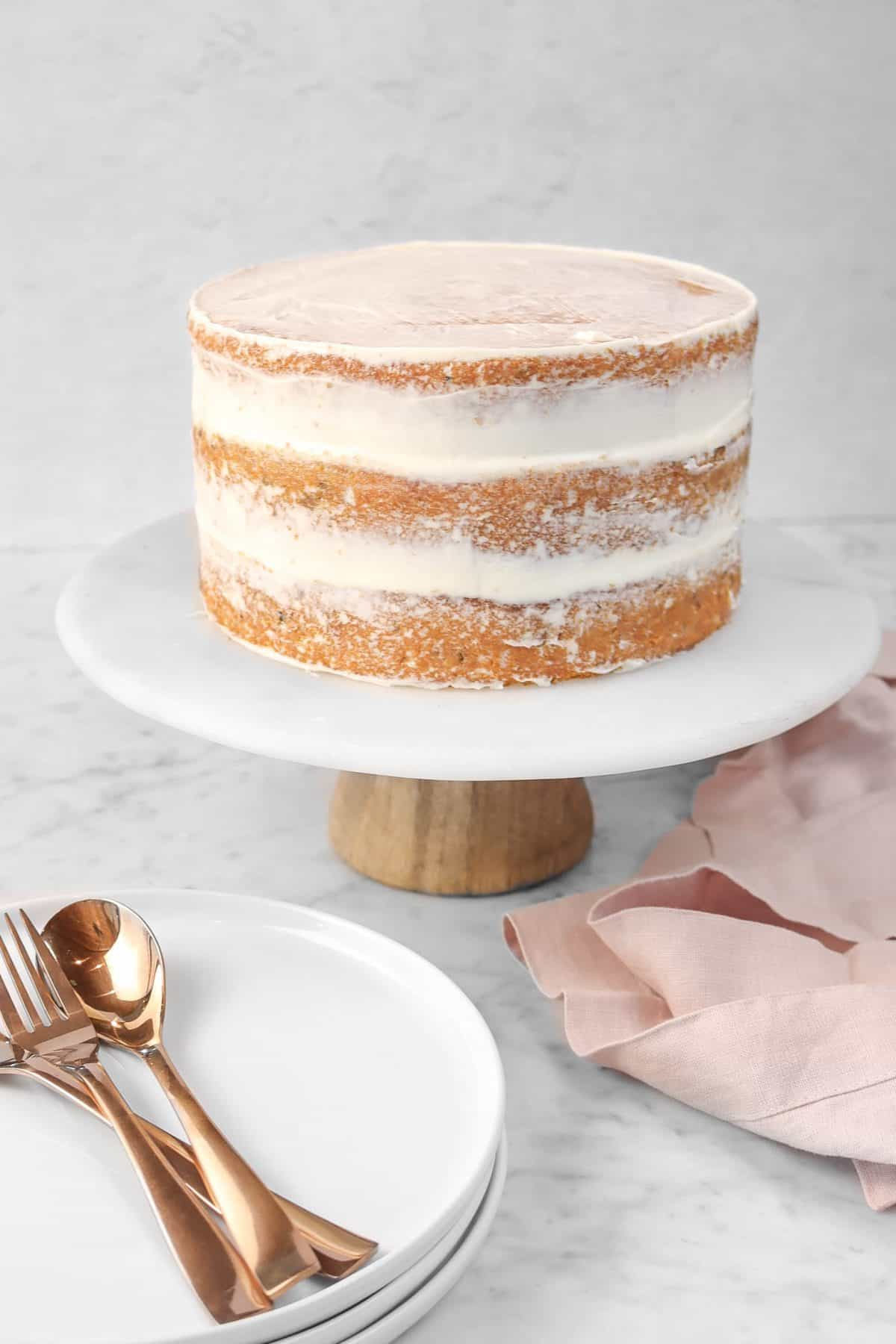 italian cream cake on a marble cake plate with three white plates, a pink napkin, and copper forks and spoons.