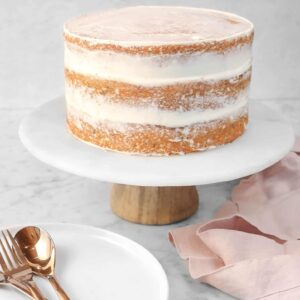 italian cream cake on a marble cake plate wit three white plates, a pink napkin, and copper forks and spoons