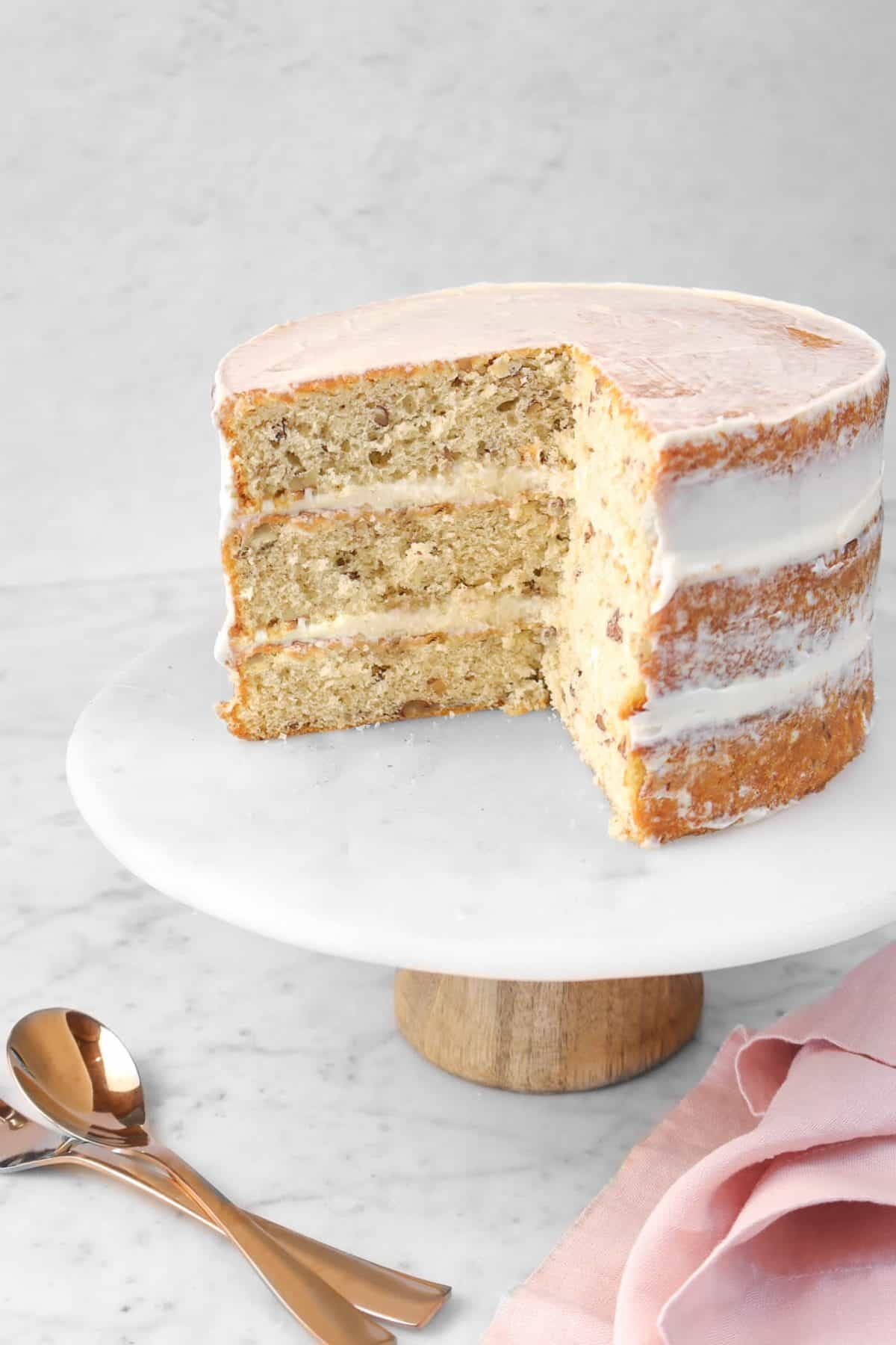italian cream cake with two slices taken out of it on a marble cake plate with a copper spoon and a pink napkin